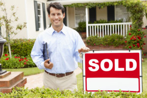 Real estate agent at work - home sold sign